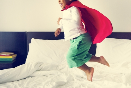 African descent kid jumping on the bed 版權商用圖片