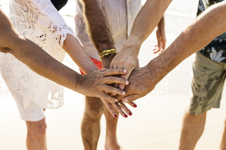 Group of senior friends stacking hands Stock Photo