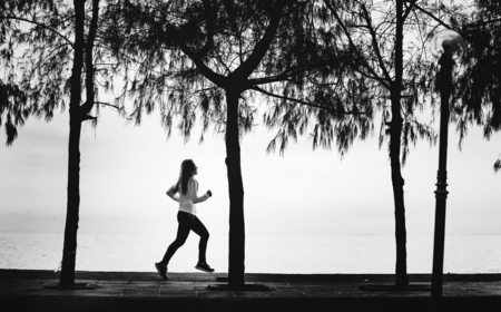 A woman jogging on a beach Stock Photo