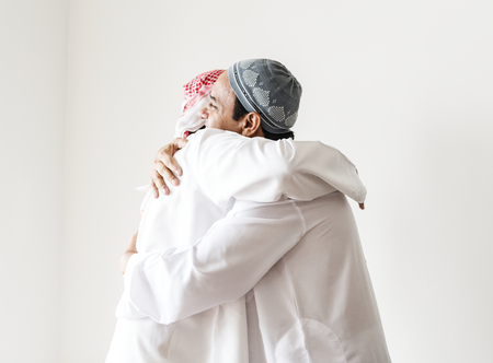 Muslim men hugging each other Stock Photo