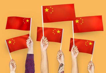 Hands waving flags of China 版權商用圖片