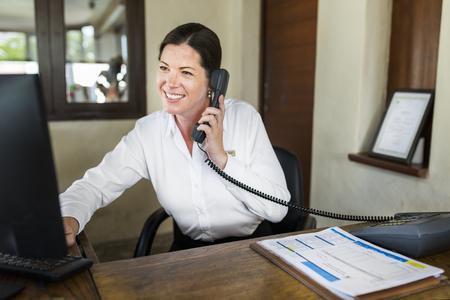 Female resort receptionist working at the front desk Reklamní fotografie - 106429234