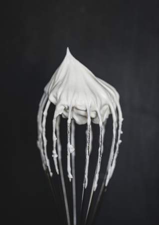 Close up of a wire whisk with whipped cream on top