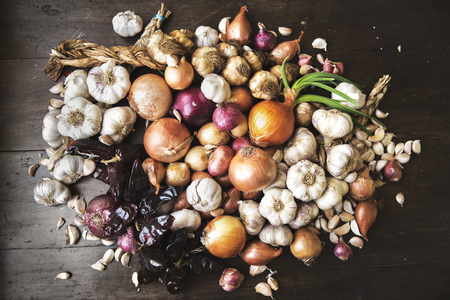 Garlics, onions, and dried chilies on wooden background