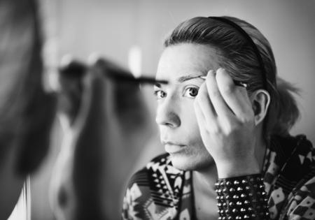 Drag queen applying makeup in a mirror