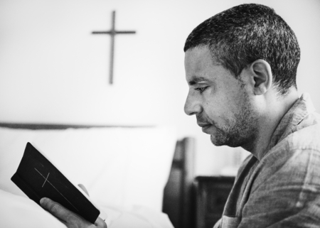 A man reading a bible alone Stock Photo
