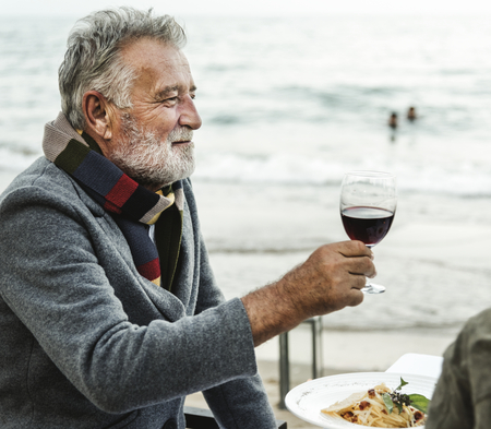 Seniors toasting with red wine at the beach Foto de archivo - 106476829
