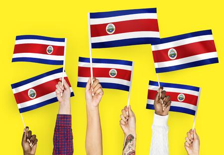 Hands waving the flags of Costa Rica 版權商用圖片 - 106476851