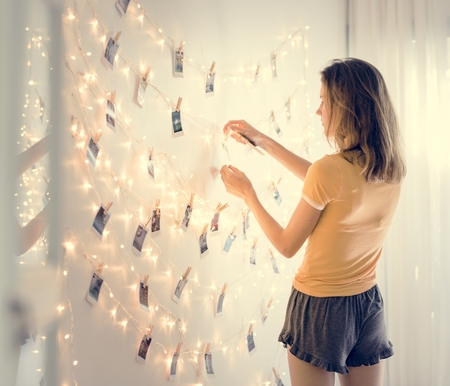 A woman looking at photos hanging on decoration lights