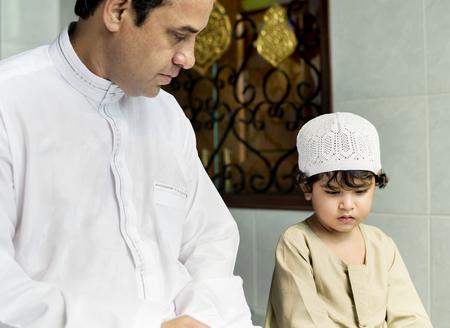 Muslim boy learning how to Salah Stock Photo