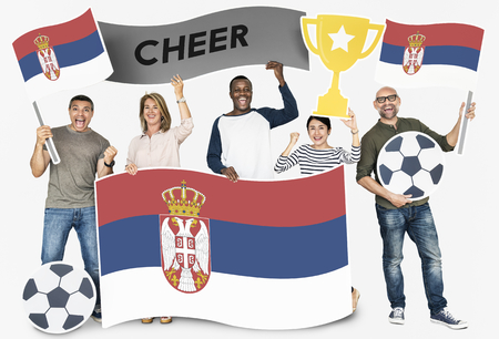 Diverse football fans holding the flag of Serbia