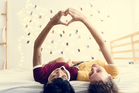 Women lying on the bed together Stock Photo