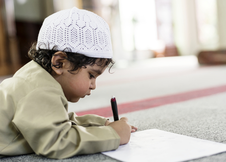 Little boy playfully drawing in a mosque during Ramadan Imagens