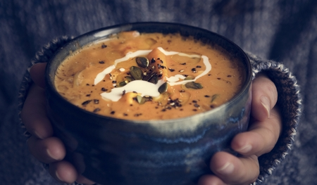 Woman holding a bowl of soup food photography recipe idea Stok Fotoğraf
