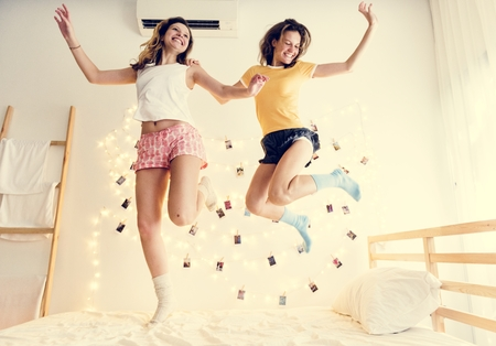 Two Caucasian women jumping on the bed together Stock Photo - 107196580