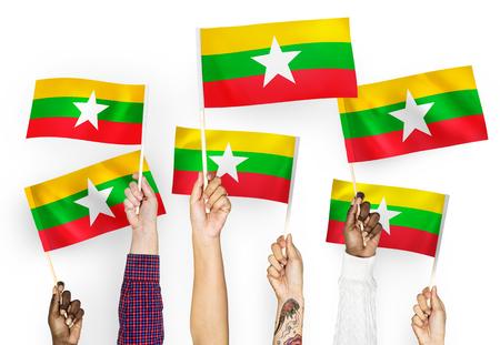 Hands waving flags of Myanmar
