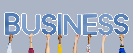 Hands holding up blue letters forming the word business