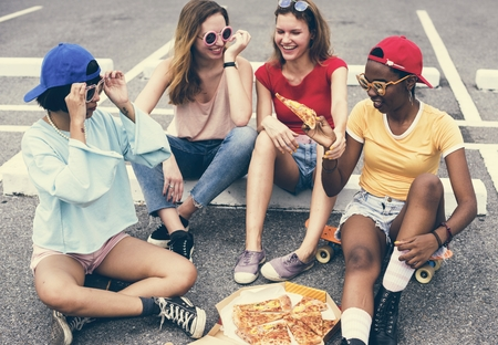 A diverse group of women sitting on the floor and eating pizza together