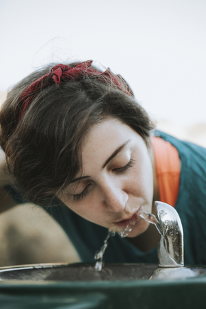 Woman drinking water from a water fountain