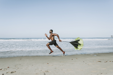 Fit man with a running parachute at the beach Stockfoto