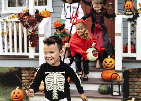 Jonge kinderen bedriegen of behandelen tijdens Halloween Stockfoto