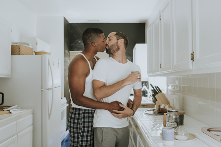 Gay couple kissing in the kitchen