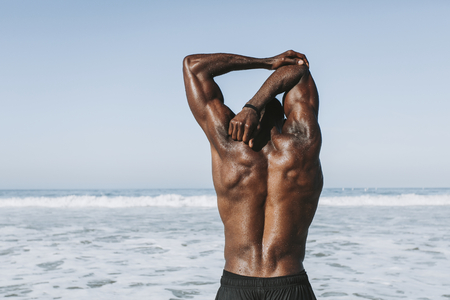 Fit man stretching at the beach Stock Photo