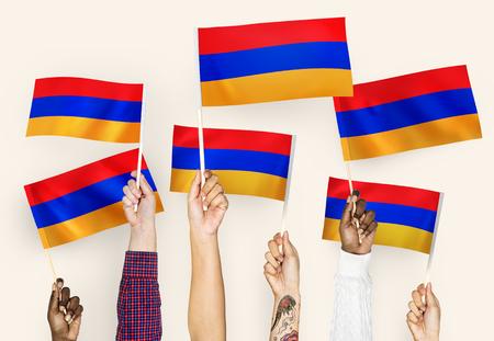 Hands waving flags of Armenia