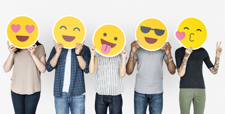 Diverse persone che tengono emoticon felici