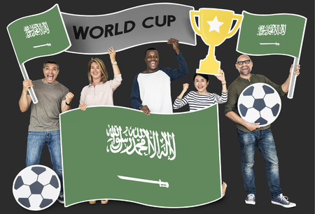 Diverse football fans holding the flag of Saudi Arabia Banque d'images