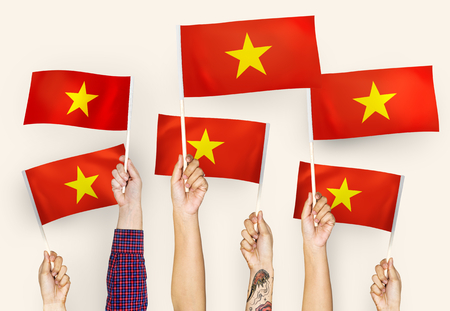 Hands waving flags of Vietnam Stock Photo