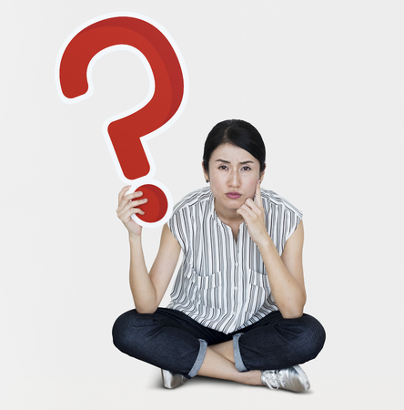 Confused woman holding a question mark icon Stock Photo