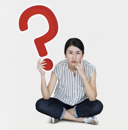 Mujer confundida sosteniendo un icono de signo de interrogación
