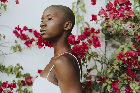 Skinhead woman surrounded by red flowers Reklamní fotografie