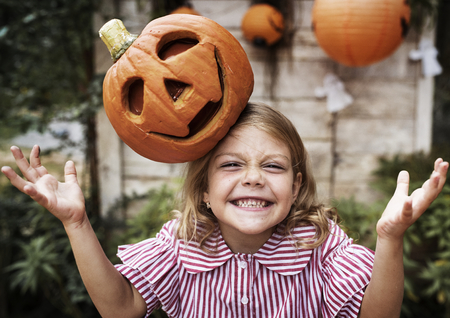 Young playful girl with her Halloween jack-o'-lantern Standard-Bild
