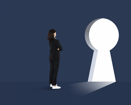 Woman standing in front of a huge keyhole Stock Photo