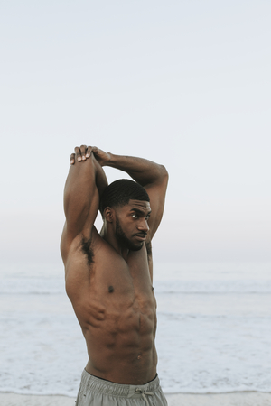 Fit man stretching at the beach Stockfoto