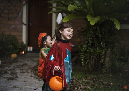 Young kids trick or treating during Halloween Stock Photo