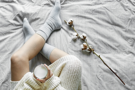 White woman sitting on bed with hot milk in winter