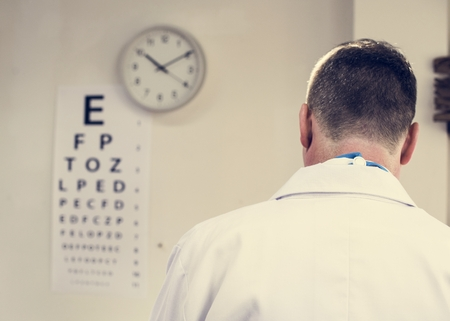 Rear view of a doctor with eye test chart on wall Foto de archivo