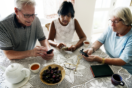 Group of diverse senior people using mobile phone