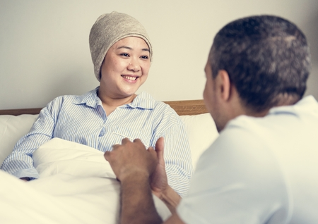 A sick woman in bed with her partner Stock Photo