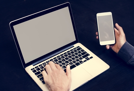Closeup of hand holding mobile phone with computer laptop background