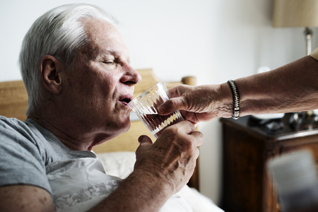 Caucasian senior man drinking water in his bed Standard-Bild - 111124651