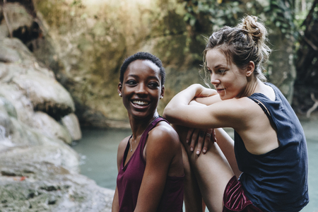 Two friends relaxing by a waterfall Stockfoto