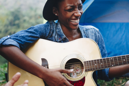 African American woman playing a guitar at a campsite Banque d'images - 111124795