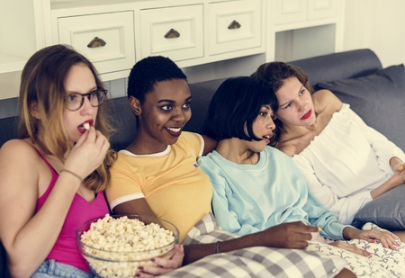 Diverse women eating popcorn together Stock Photo