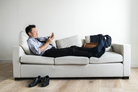 Asian businessman taking break laying on couch 免版税图像