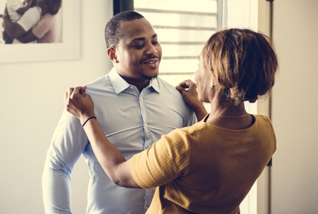 Black wife helping husband dress up for work