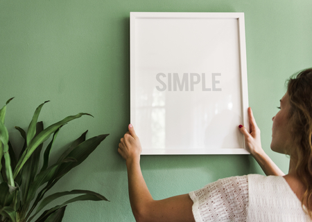 Chica colgando un marco en una pared verde
